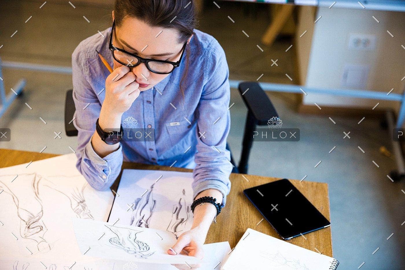 pensive-woman-fashion-designer-sitting-and-PHGZYEM